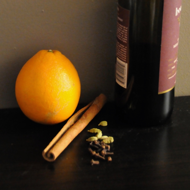 bottle of red wine, orange, cinnamon stick, cloves and cardamom pods