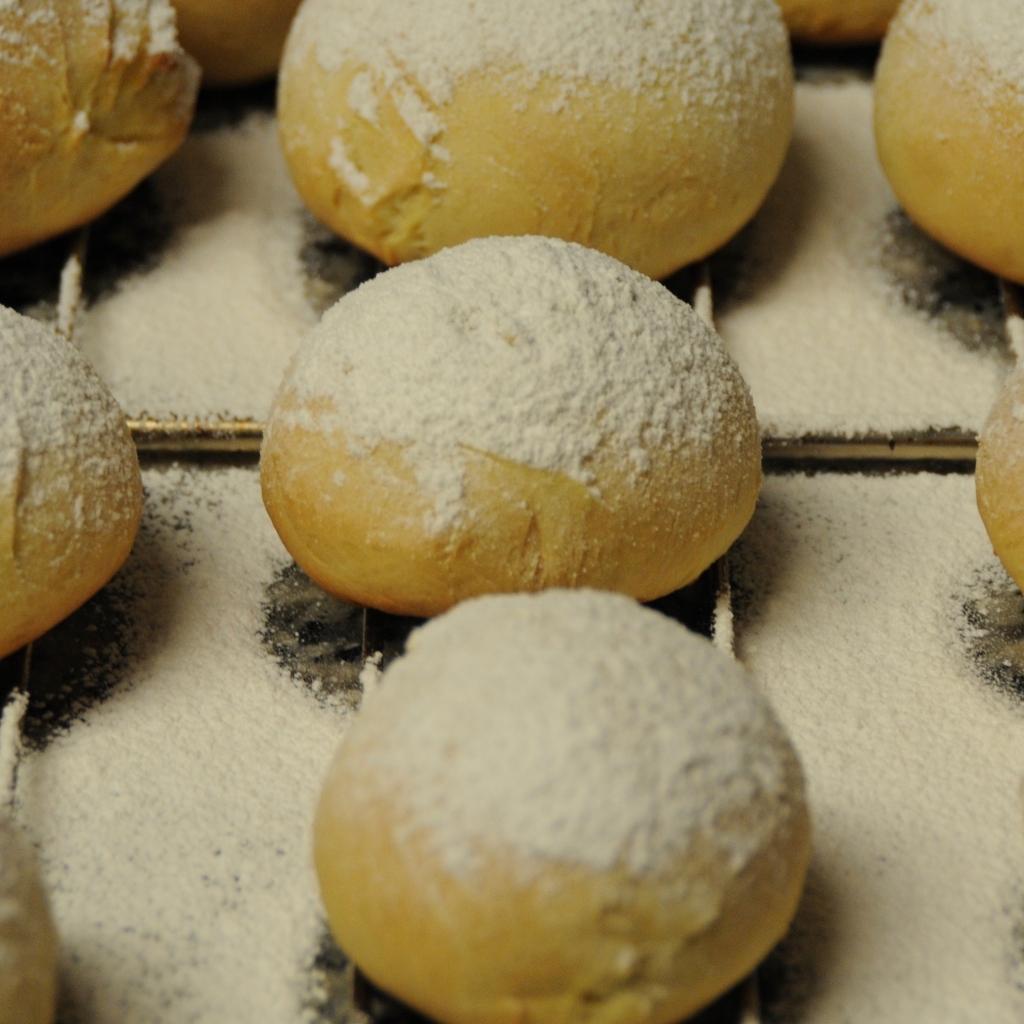 """several  """"Berliner"""" (filled German donuts) cooling on a cooling rack"""