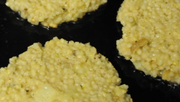 Parsnip and millet burgers sizzling in a pan