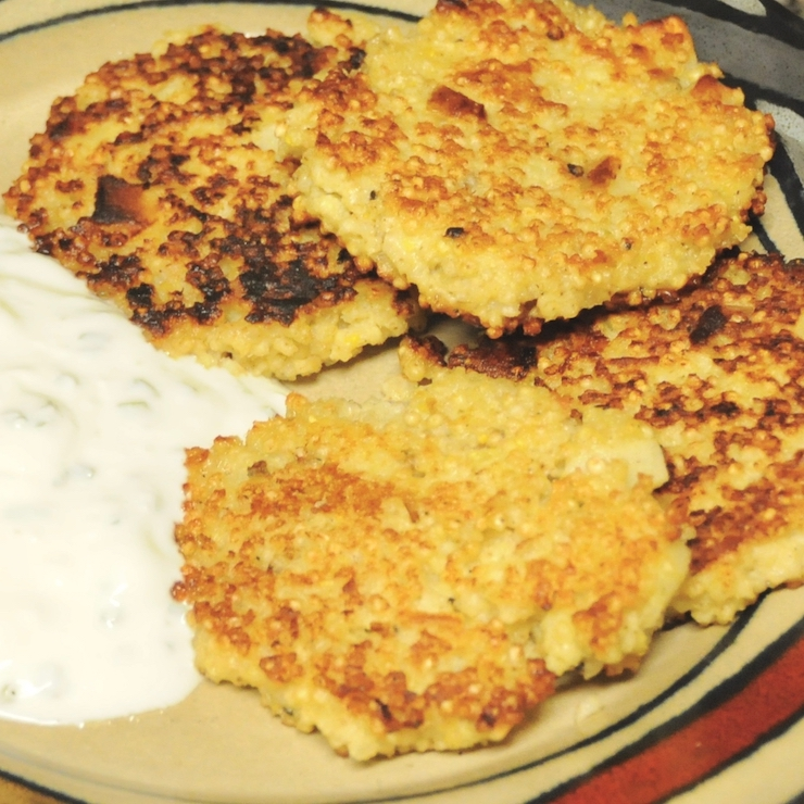 millet and parsnip burgers on a plate with sour cream dip