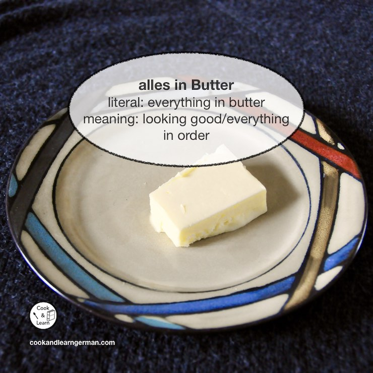 """A piece of butter on a plate, a speech bubble says: """"alles in Butter - literal: everything in butter - meaning: looking good/everything in order"""""""