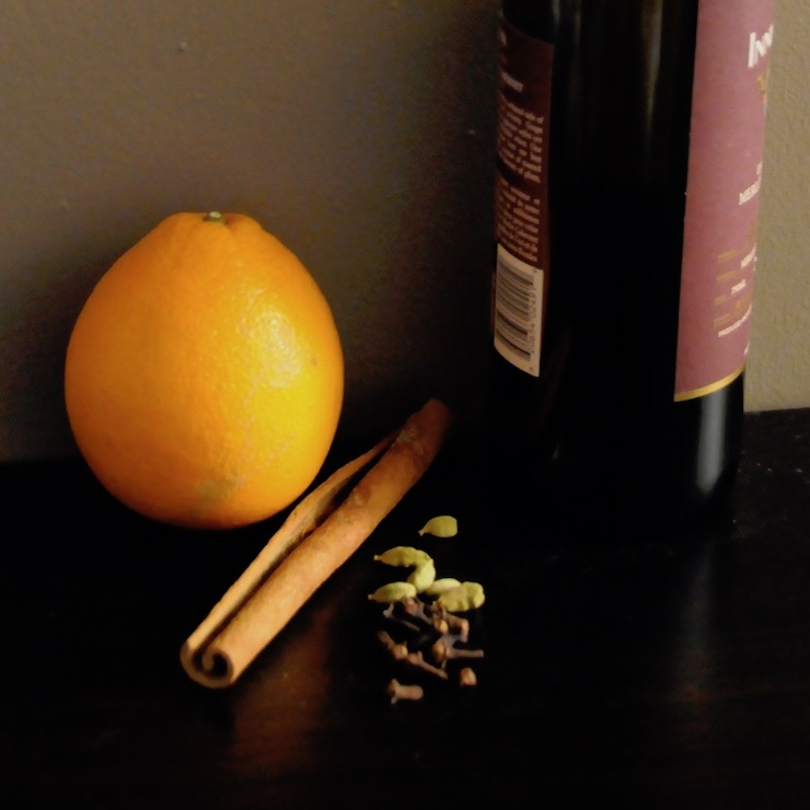 bottle of red wine, orange, cinnamon stick, cloves and cardamom pods