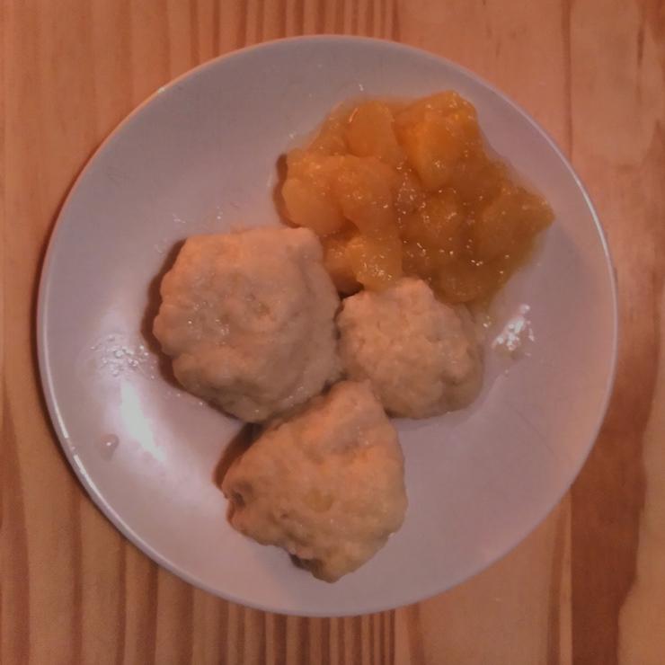 3 German potato dumplings (Kartoffelklöße) on a plate with apple compote