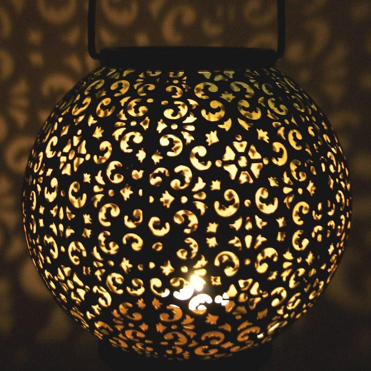 a lit lantern with an intricate pattern