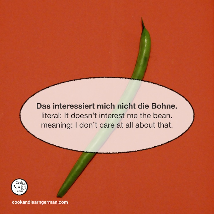 """A single green bean. A speech bubble says: """"Das interessiert mich nicht die Bohne. - Literal: It doesn't interest me the bean. - Meaning: I don't care at all about that."""""""