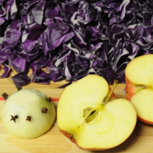 Shredded red cabbage, a halved apple and a clove-studded onion half